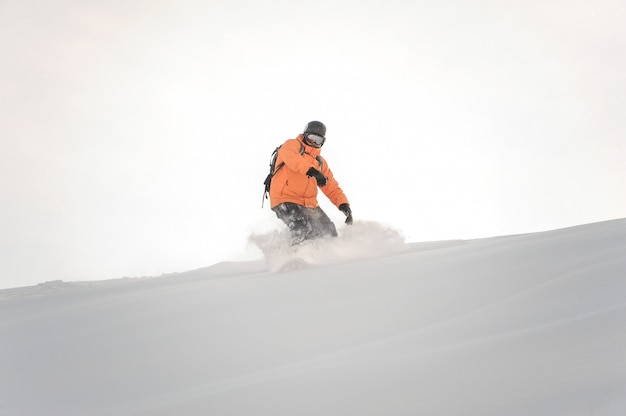 白い空を背景に山の斜面を下って乗るオレンジ色のスポーツウェアのスノーボーダー