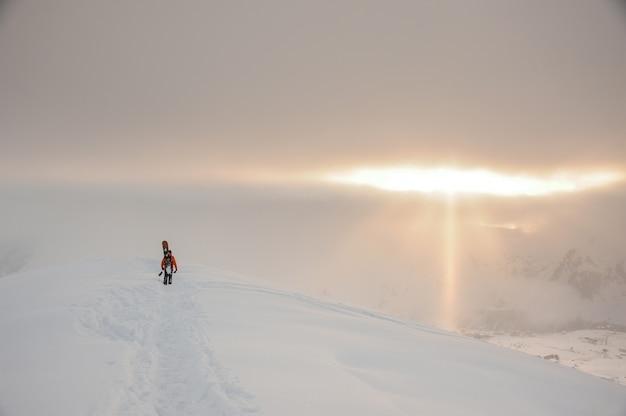 山の頂上でボードを歩いてスノーボーダー