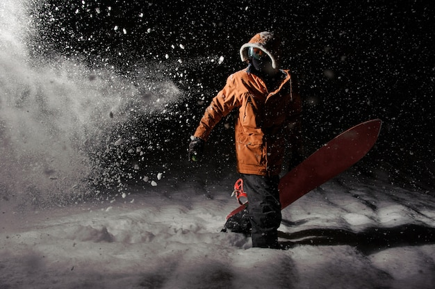 夜のボードとオレンジ色のスポーツウェアのプロのスノーボーダー