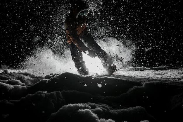 Активный сноубордист в спортивной одежде, прыжки на доске ночью