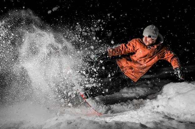 Молодой сноубордист в оранжевой спортивной одежде прыгает на доске ночью