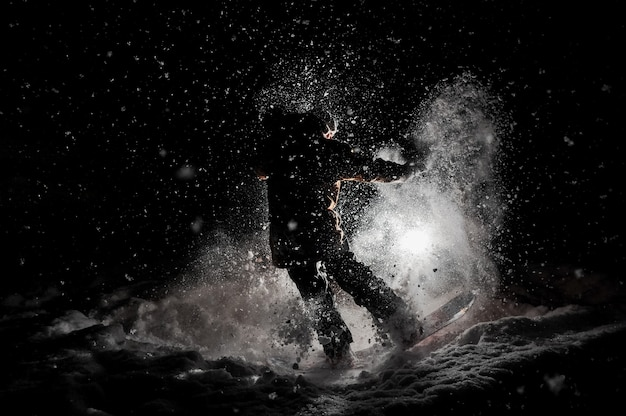 Сноубордист в спортивной одежде прыгает на доске ночью