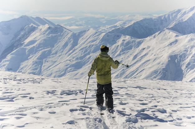 Вид сзади активного лыжника в ярко-желтой спортивной одежде, едущей по горам