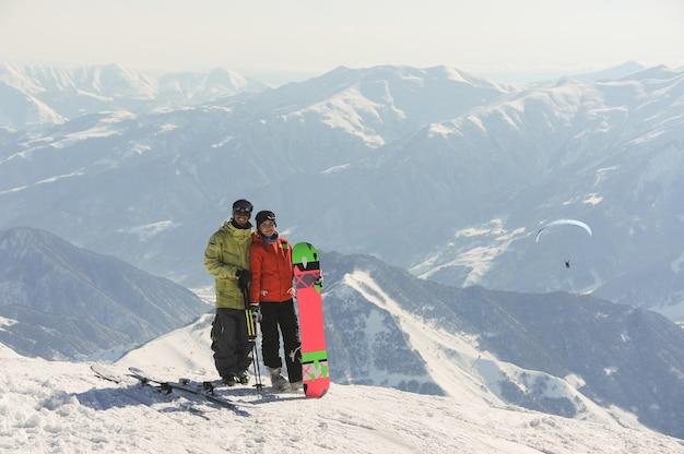 Пара сноубордистов в яркой спортивной одежде, стоя на высоких горах