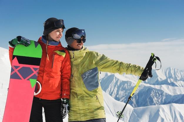 Девушка сноубордист и лыжник, наслаждаясь снежный пейзаж гор в гудаури, грузия