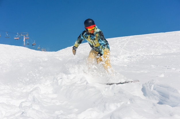 Профессиональный активный сноубордист в яркой спортивной одежде катается по склону горы