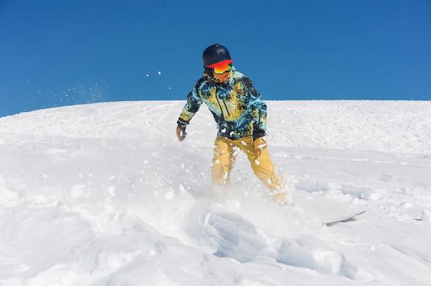 山の斜面を下る明るいスポーツウェアでプロのスノーボーダー