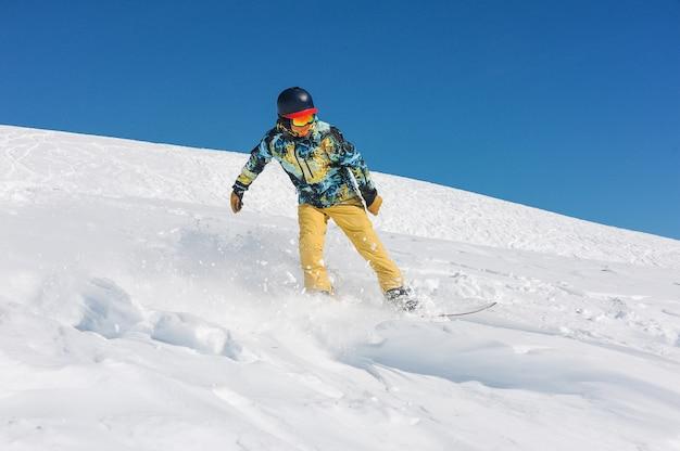 山の斜面に乗って明るいスポーツウェアでプロの男性スノーボーダー