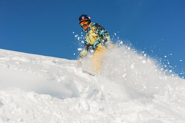 Активный профессиональный сноубордист в яркой спортивной одежде катается по склону пороховой горы