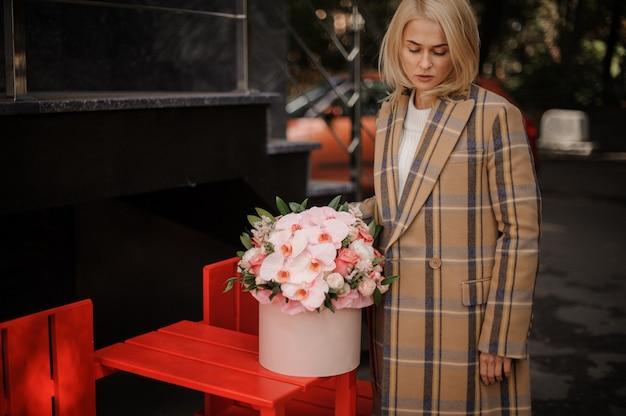 花のピンクのボックスと格子縞の秋コートのブロンドの女性
