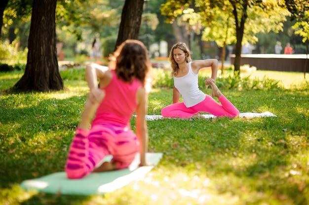 曲がった猿のポーズで公園でヨガを練習する女の子