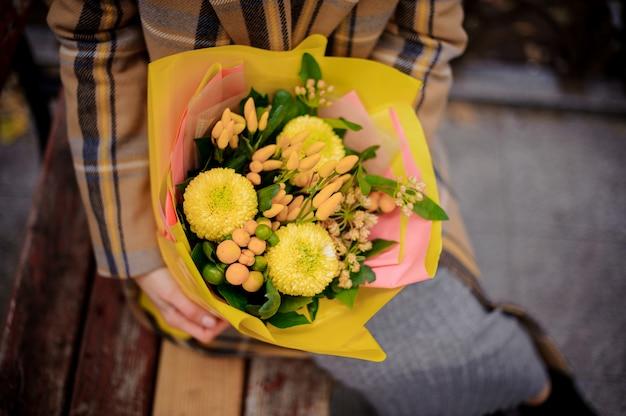 黄色の花の花束とベンチに座っている格子縞のコートの女性のトップビュー