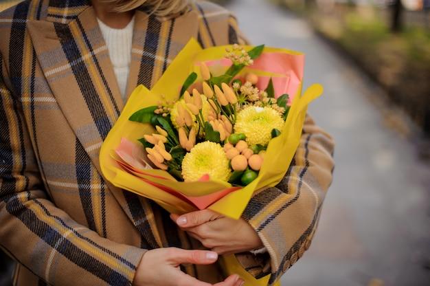 明るい黄色の花の花束を保持している格子縞のコートの女性