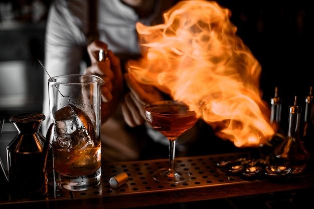 カクテルグラスにライターから火を入れて男性バーテンダー