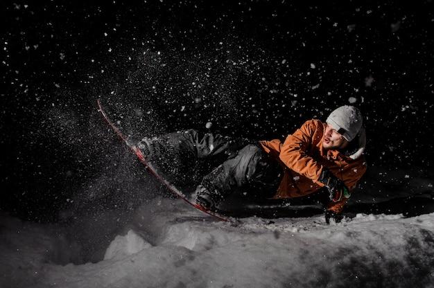 Молодой сноубордист в оранжевой куртке верхом на снежном холме ночью