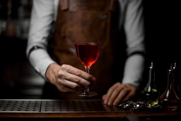 ガラスの赤いアルコールカクテルを提供するプロのバーテンダー