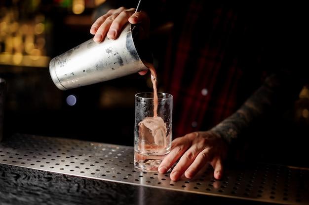 バーテンダーがグラスに甘いジューシーなカクテルを注ぐ