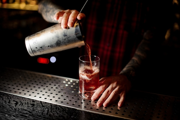 ミクソロジストが甘いジューシーなカクテルをグラスに注ぐバー