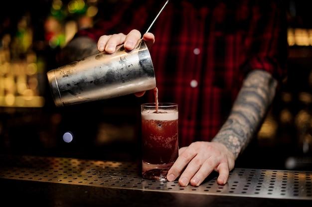 入れ墨のあるバーテンダーがグラスにグラスに甘いジューシーなカクテルを注ぐ