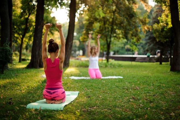 心を落ち着かせるポーズで公園でヨガを練習する女の子