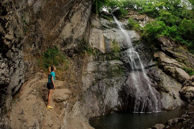 スポーツウェアの女性観光客が滝のそばに立つ