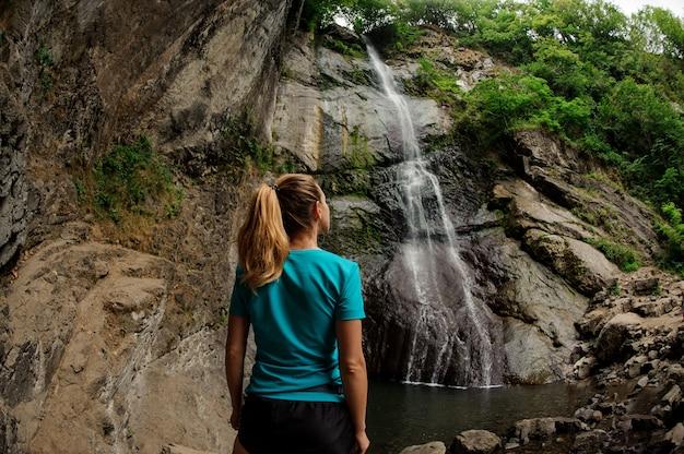 滝の近くに立っているスポーツウェアの女性観光客