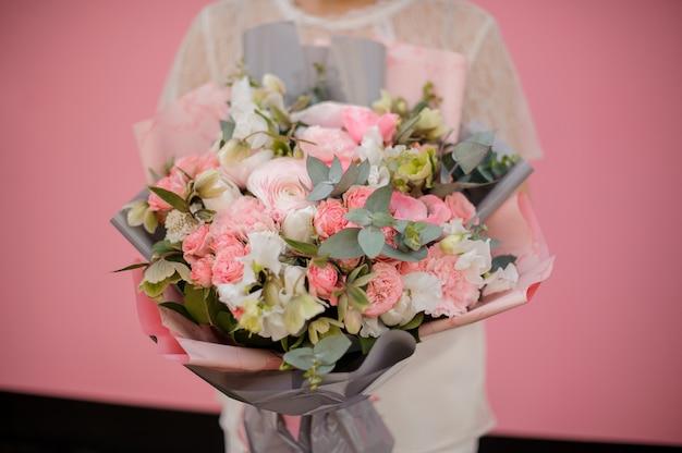 Букет из разных цветов в серо-розовой бумаге