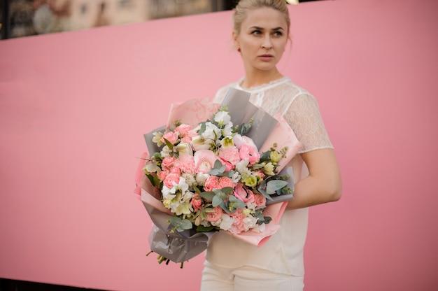 Молодая девушка держит букет в серо-розовой бумаге