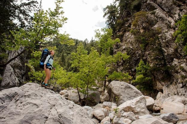 女性ハイカーは峡谷の岩を旅行します