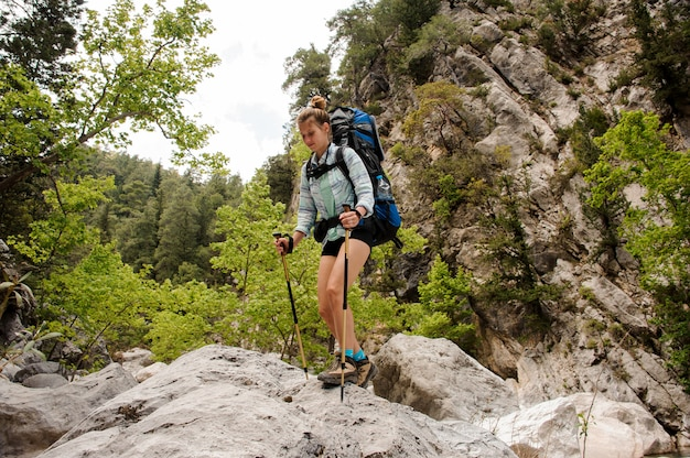 Путешественник женского пола, путешествующий через скалы в каньоне