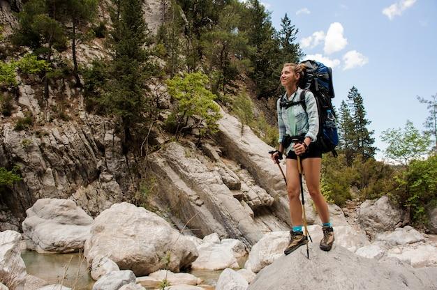 女性ハイカーは峡谷の石の上に立つ