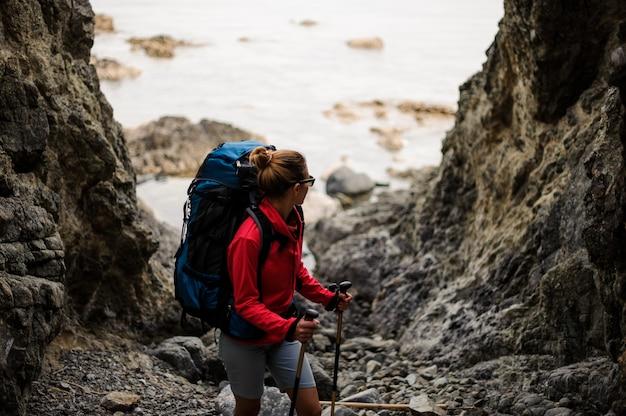 バックパックを持つ女性ハイカーは岩の間に立っています