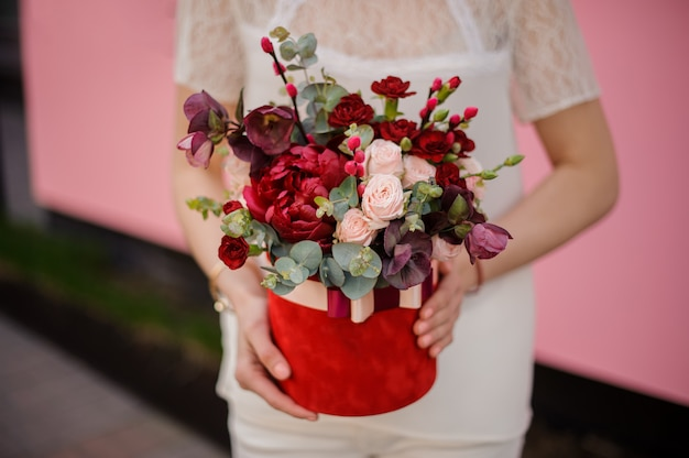 帽子ボックスに花束を持って女の子のショットを閉じる