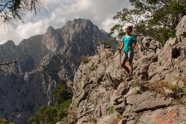Молодая девушка позирует на вершине горы