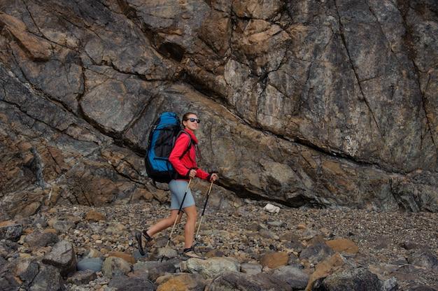崖の前を歩く女性旅行者