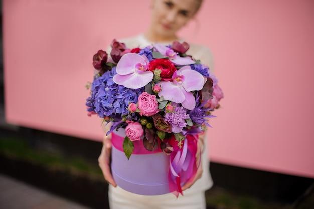 弓と帽子ボックスで花束を持って女の子のクローズアップ