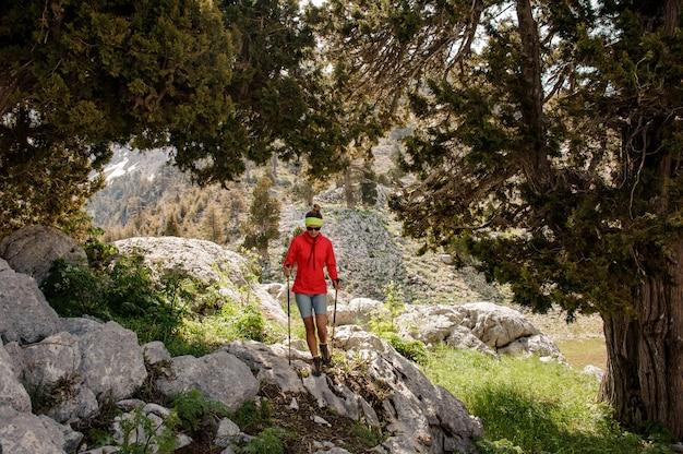 森の中でのハイキング用具を持つ女性観光客