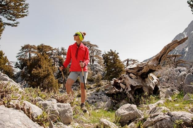 岩の間でハイキング用具を持つ女性観光客