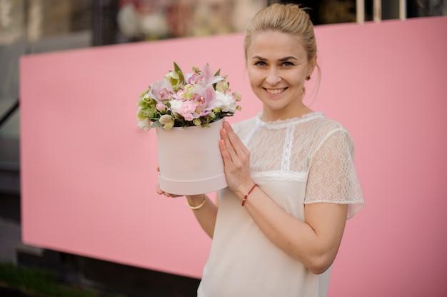 Улыбающаяся девушка держит букет в розовой шляпной коробке