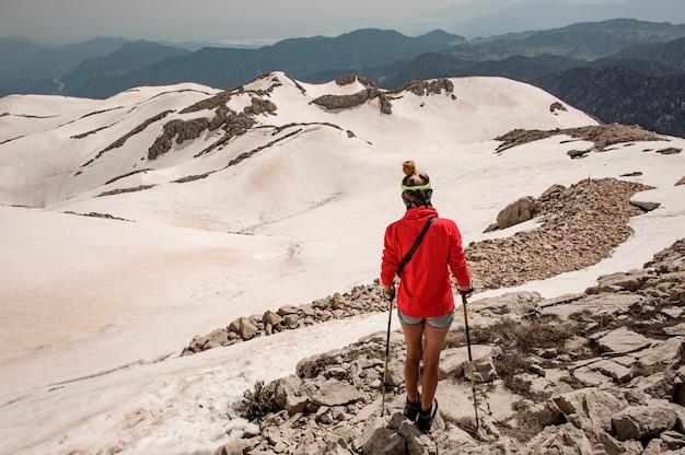 山の杖を持つ女性登山家
