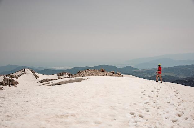 女性ハイカーが山で杖と旅します。