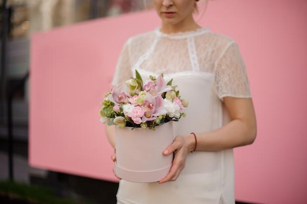 Крупный план девушка держит букет в розовой шляпной коробке
