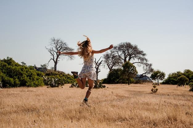 Молодая девушка в легком платье прыгает на поле