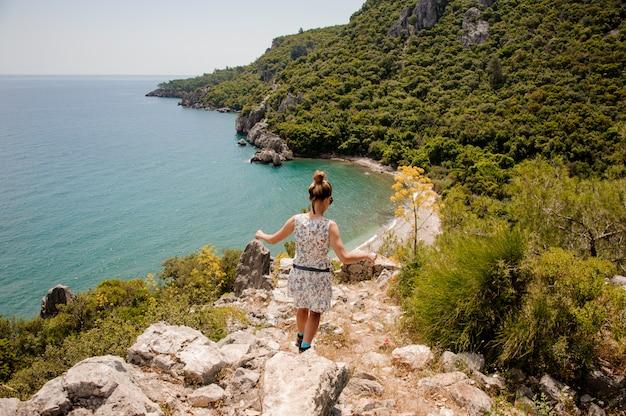 Молодая женщина в платье стоит на горе