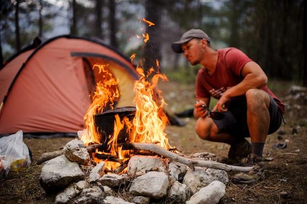 Мужской турист разжигает костер перед палаткой