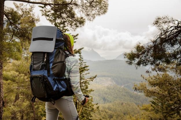 Женский турист с рюкзаком смотрит на долину