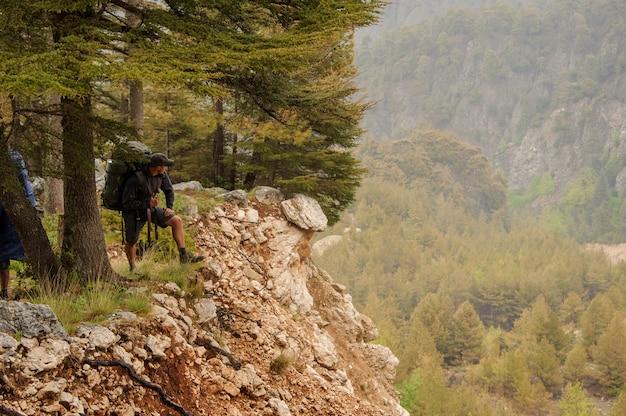 バックパックを持つ男性は崖の上に立つ
