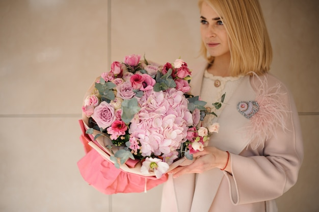花の素晴らしい花束を持つ若い女性