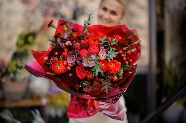 女の子は完全に赤い花束と立っています。