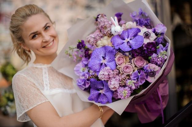 完全に紫色の花束を持つ少女が立っています。
